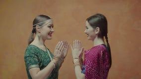 Mujeres en sari que se dan la bienvenida durante el encuentro almacen de metraje de vídeo