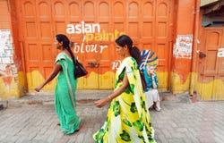 Mujeres en sari tradicional que caminan en la calle con las paredes pintadas Imagen de archivo libre de regalías