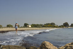 Mujeres en sombrero que caminan descalzo en la orilla de mar Fotos de archivo