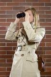 Mujeres en un trenchcoat con los prismáticos fotografía de archivo