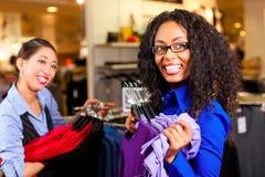 Mujeres en una alameda de compras con ropa Imagen de archivo
