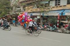 Mujeres en una bicicleta con los globos coloridos en la calle. Hanoi. Vietnam foto de archivo
