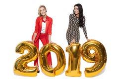 Mujeres encantadoras que llevan a cabo los números de oro grandes 2019 Feliz Año Nuevo Fotografía de archivo libre de regalías