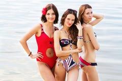 Mujeres encantadoras que tienen un resto en la playa Fotografía de archivo