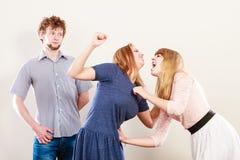 Mujeres enojadas agresivas que luchan sobre hombre Foto de archivo libre de regalías