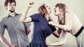 Mujeres enojadas agresivas que luchan sobre hombre Fotografía de archivo libre de regalías