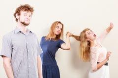 Mujeres enojadas agresivas que luchan sobre hombre Imágenes de archivo libres de regalías