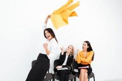 Mujeres enojadas que miran al colega feliz de la señora Foto de archivo