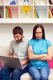 Sentada enojada de la mujer mientras que su marido Foto de archivo