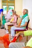 Mujeres entusiastas que hacen ejercicios en sillas Imagenes de archivo