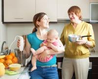 Mujeres felices con el niño junto que cocina el puré de la fruta imagenes de archivo