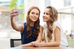Mujeres felices con el smartphone que toma el selfie en el café Imagenes de archivo
