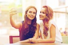 Mujeres felices con el smartphone que toma el selfie en el café Imagen de archivo