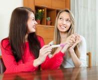Mujeres felices con la prueba de embarazo en la tabla Fotografía de archivo libre de regalías