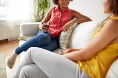 Mujeres felices con las bebidas que hablan en casa Fotografía de archivo