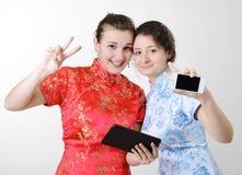 Mujeres felices con los dispositivos móviles Imágenes de archivo libres de regalías