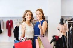 Mujeres felices con los panieres en la tienda de la ropa Imagen de archivo libre de regalías