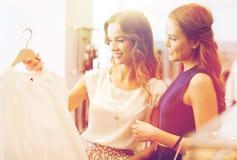 Mujeres felices con los panieres en la tienda de la ropa Foto de archivo libre de regalías