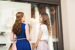 Mujeres felices con los panieres en la ventana de la tienda Foto de archivo libre de regalías