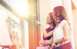 Mujeres felices con los panieres en la ventana de la tienda Fotografía de archivo
