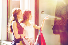 Mujeres felices con los panieres en la ventana de la tienda Imagen de archivo libre de regalías