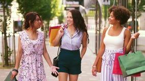 Mujeres felices con los panieres que caminan en ciudad metrajes