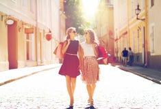 Mujeres felices con los panieres que caminan en ciudad Fotografía de archivo