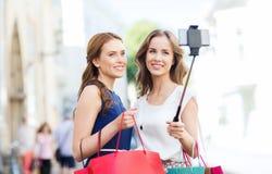 Mujeres felices con los panieres y smartphone Foto de archivo