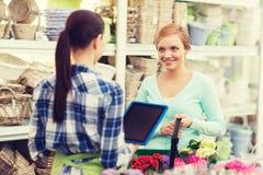 Mujeres felices con PC de la tableta en la floristería Foto de archivo