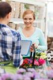 Mujeres felices con PC de la tableta en la floristería Fotos de archivo
