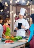 Mujeres felices con PC del cocinero y de la tableta en cocina Imágenes de archivo libres de regalías