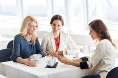 Mujeres felices con smartphone en el restaurante foto de archivo libre de regalías