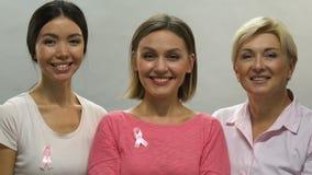 Mujeres felices de diversa edad que apoyan la campaña anticáncer, cintas rosadas almacen de video