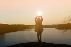 Mujeres felices de la silueta en la puesta del sol Imagen de archivo