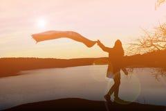 Mujeres felices de la silueta en la puesta del sol Imagen de archivo libre de regalías