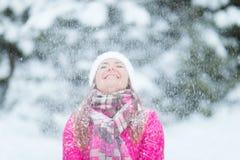Mujeres felices del invierno en luces de la Navidad de la nieve del parque Foto de archivo libre de regalías