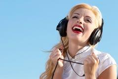 Mujeres felices en auriculares Imágenes de archivo libres de regalías