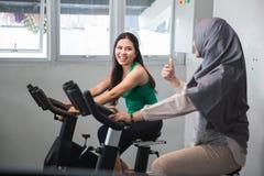 Mujeres felices en el gimnasio que hace ejercicios cardiios Imagen de archivo libre de regalías