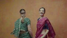 Mujeres felices en la sari india que gira en danza almacen de metraje de vídeo