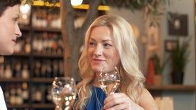 Mujeres felices que beben el vino en la barra o el restaurante almacen de metraje de vídeo