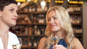 Mujeres felices que beben el vino en la barra o el restaurante metrajes
