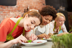 Mujeres felices que cocinan y que adornan platos Foto de archivo
