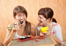 Mujeres felices que comen los rodillos de sushi Imagen de archivo libre de regalías