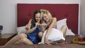 Mujeres felices que compran en tienda en línea usando la tableta almacen de metraje de vídeo