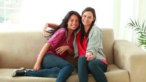 Mujeres felices que corren entonces sentarse en un sofá almacen de video