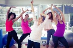 Mujeres felices que ejercitan con los brazos aumentados mientras que mira para arriba Fotografía de archivo libre de regalías