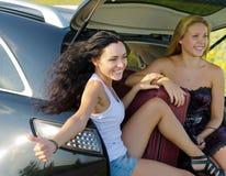 Mujeres felices que hacen autostop de la parte posterior del coche Fotos de archivo