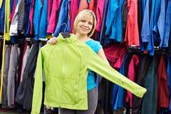 Mujeres felices que hacen compras para la ropa de deportes en tienda Foto de archivo
