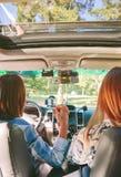Mujeres felices que llevan a cabo las manos dentro del coche Fotos de archivo libres de regalías