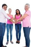 Mujeres felices que llevan las cintas del cáncer de pecho que ponen las manos juntas Imágenes de archivo libres de regalías
